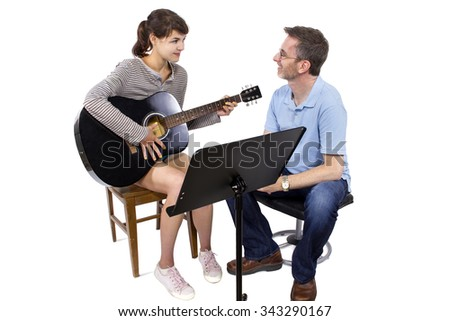 Music teacher tutoring young female student how to play guitar.  They are isolated on a white background. - stock photo