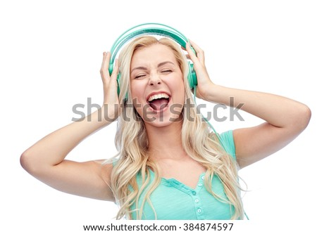 music, technology and people concept - happy young woman or teenage girl with headphones singing song - stock photo