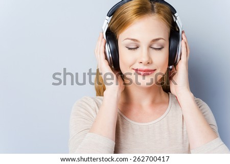 Music waves. Beautiful young women in headphones keeping eyes closed and smiling while standing against grey background - stock photo