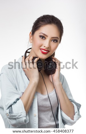 Music. Woman holding big earphones headphones listening to music on mp3 player. Playful happy smiling young mixed race Asian Caucasian woman isolated on white background. - stock photo