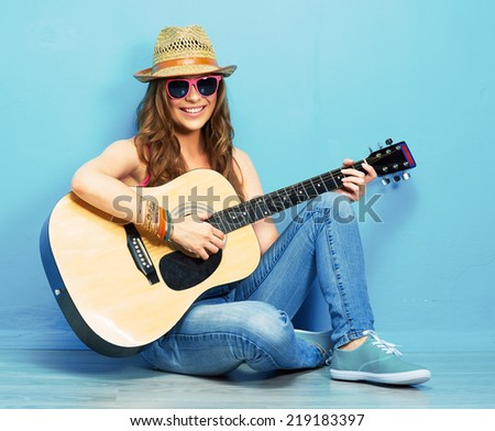 Music woman portrait with guitar. Blue background. - stock photo
