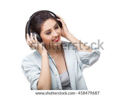 Music. Woman with big earphones headphones listening to music on mp3 player. Playful happy smiling young mixed race Asian Caucasian woman isolated on white background. - stock photo