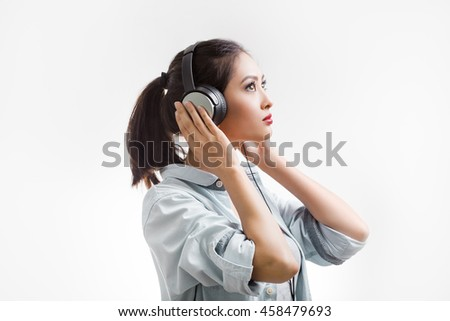 Music. Woman with big earphones headphones listening to music on mp3 player. Young mixed race Asian Caucasian woman isolated on white background. - stock photo