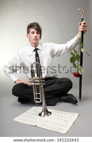 Music. Young man in love with trumpet note sheet red rose on gray background - stock photo