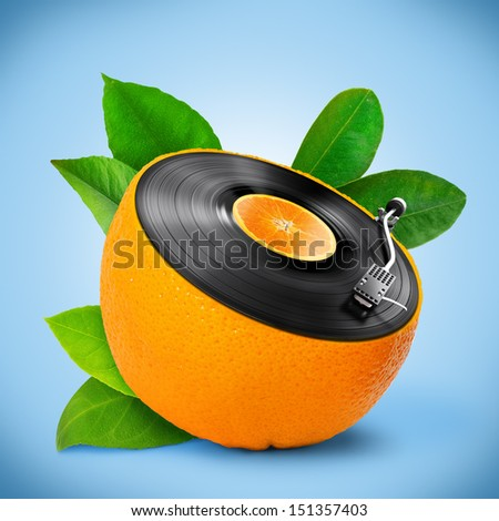 Musical background with a vinyl disc and orange. - stock photo