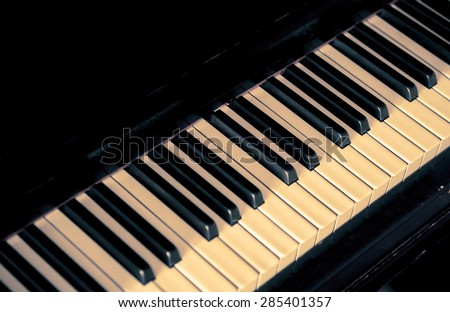 Musical background with piano keys. Music concept with old classic musical jazz instrument. Piano keys in retro style with copy-space for text on black color background. - stock photo