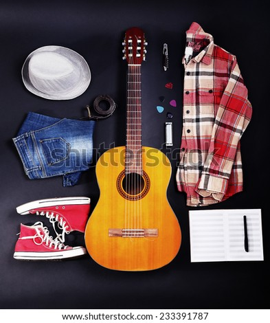 Musical equipment, clothes and footwear on dark background - stock photo