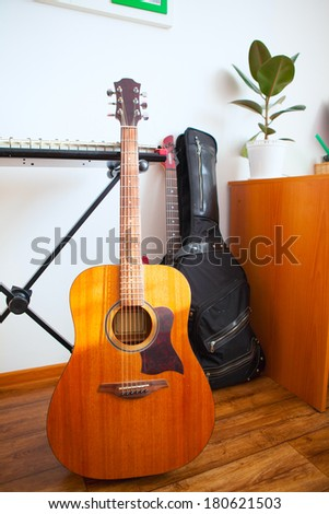 Musical instruments are near the white wall of the apartment. acoustic guitar, synthesizer and electric guitar at the front. - stock photo