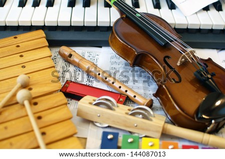 Musical instruments for children: xylophone, children's violin, tambourine, flute, harmonica, piano keyboard. - stock photo