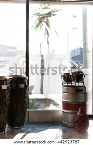 Musical instruments including bongo and drums in a room beside a glass window  which can bee seen the outside - stock photo