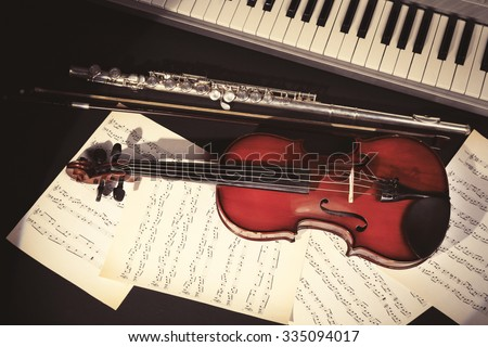 Musical instruments with music notes on dark background - stock photo