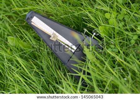 musical metronome on a grass - stock photo