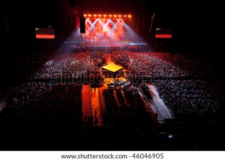 musical performance concert. red one light. light show. group band singer is performing dancing on stage. bright lights above stage. - stock photo