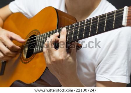 musician , guitarist plays classical / acoustic guitar - stock photo