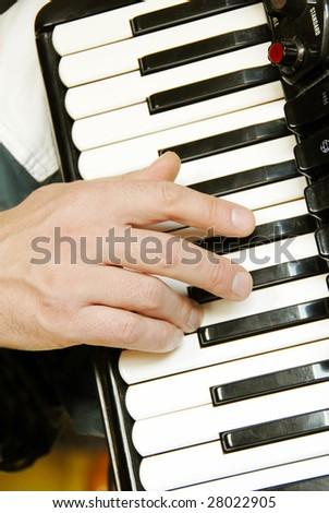 musician hand playing accordion closeup in dramatic shadows - stock photo