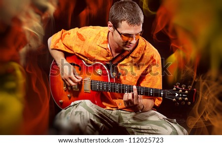 Musician Man playing electronic guitar at bright background - stock photo