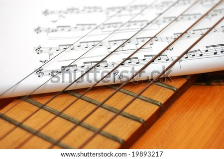 Musician notes under Spanish guitar's strings - stock photo