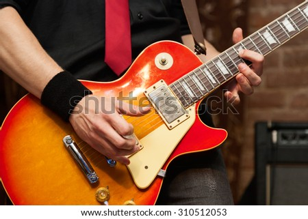 Musician performs solo on electric guitar. Close-up, shallow depth of field - stock photo