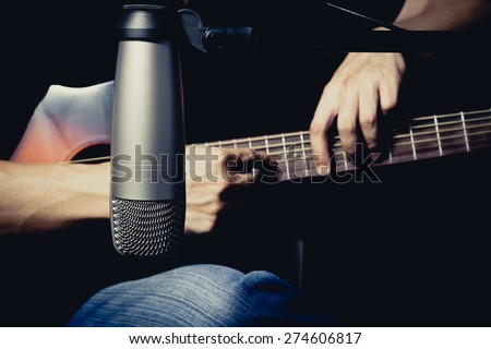 musician play acoustic guitar behind studio condenser microphone, focus to mic / for music recording concept on black background - stock photo