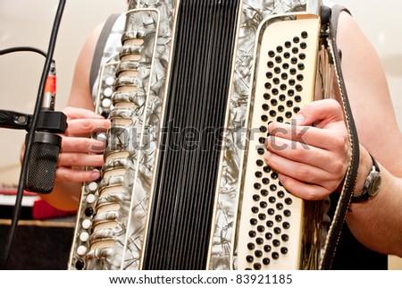 musician playing accordion in studio - stock photo
