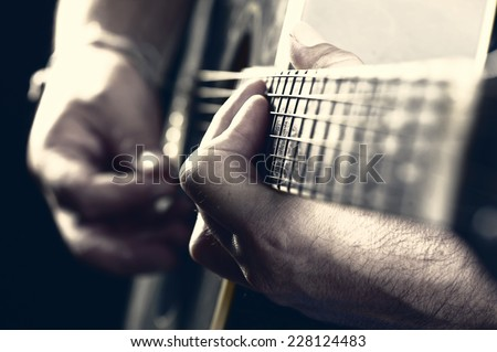 musician playing acoustic guitar and singing, on dark background   - stock photo
