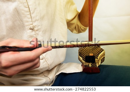 Musician playing in the Chinese folk instrument erhu. Vertical photo - stock photo
