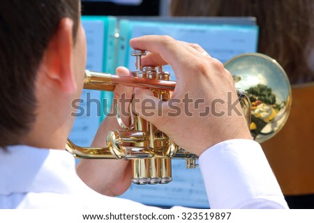 Musician playing on gold trumpet in street orchestra - stock photo