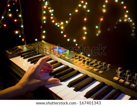 Musician playing on musical keyboard (Close up of a hand playing a MIDI controller keyboard in black background) - stock photo