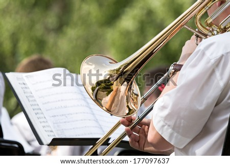 Musician playing the trombone in orchestra - stock photo
