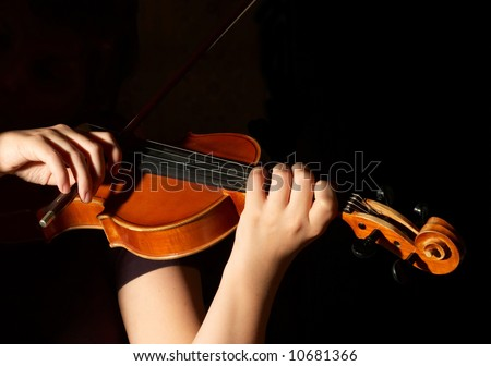 Musician playing violin isolated on black - stock photo