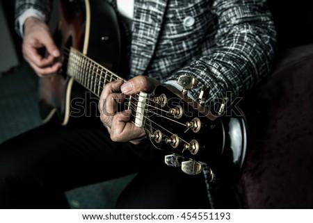 Musician plays guitar, close up - stock photo