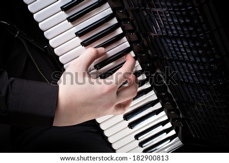 musician plays the accordion. Musician makes glissando or cluster - stock photo