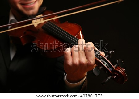 Musician plays violin on black background, close up - stock photo