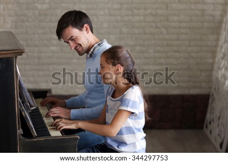 Musician teacher and little girl play piano together - stock photo