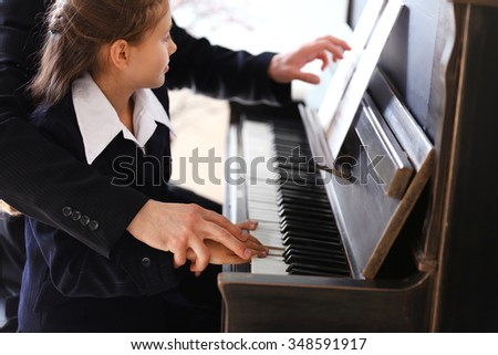 Musician teacher trains to play piano little girl, close up - stock photo