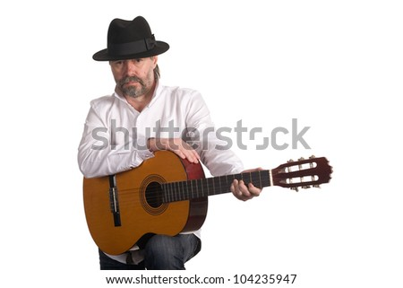 Musician with a guitar in a black hat. - stock photo