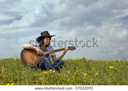 musician with guitar in a field - stock photo