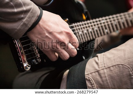 musician with guitar on black background - stock photo