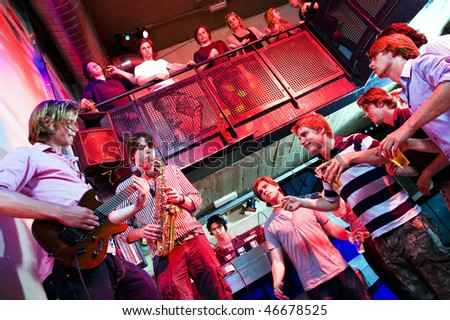 Musicians on Guitar and Saxophone, accompanied by a DJ, performing in a nightclub - stock photo