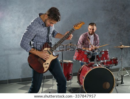 Musicians playing musical instruments in a studio - stock photo