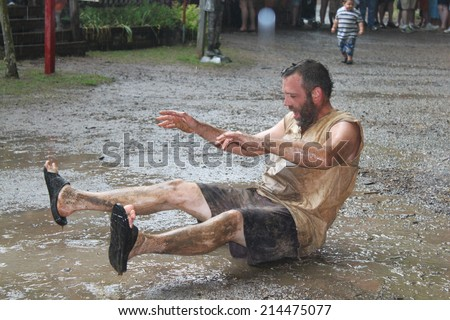 MUSKOGEE, OK - MAY 24: Grown men play in water and mud after rain at the Oklahoma 19th annual Renaissance Festival on May 24, 2014 at the Castle of Muskogee in Muskogee, OK.  - stock photo