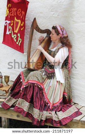 MUSKOGEE, OK - MAY 24: Woman dressed in vintage clothes plays harp at the Oklahoma 19th annual Renaissance Festival on May 24, 2014 at the Castle of Muskogee in Muskogee, OK  - stock photo