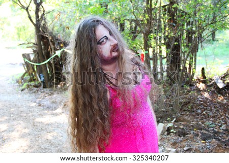 MUSKOGEE, OK - Sept. 12: A young woman dressed as a zombie scares athletes during the Castle Zombie Run at the Castle of Muskogee in Muskogee, OK on September 12, 2015.   - stock photo