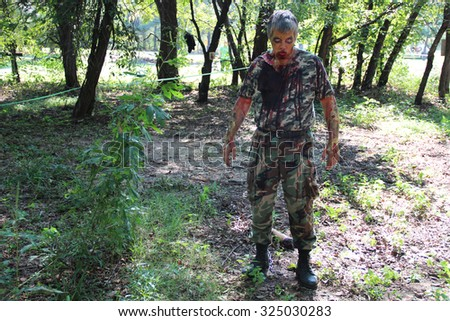 MUSKOGEE, OK - Sept. 12: An actor dressed as a zombie hides in a field and waits for the next runner during the Castle Zombie Run at the Castle of Muskogee in Muskogee, OK on September 12, 2015.   - stock photo