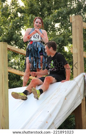 MUSKOGEE, OK - Sept. 13: An athlete slides into a muddy pit to avoid zombies during the Castle Zombie Run at the Castle of Muskogee in Muskogee, OK on September 13, 2014.  - stock photo