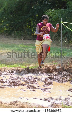 MUSKOGEE, OK - Sept. 14: Athletes run through mud and avoid zombies during the Castle Zombie Run at the Castle of Muskogee in Muskogee, OK on September 14, 2013. - stock photo
