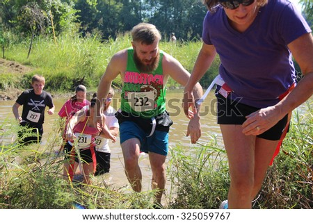 MUSKOGEE, OK - Sept. 12: Runners go through obstacles to avoid bloody zombies during the Castle Zombie Run at the Castle of Muskogee in Muskogee, OK on September 12, 2015.  - stock photo