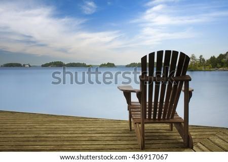Muskoka chair facing a calm lake on a wooden dock - stock photo