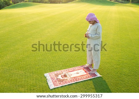 Muslim Arabic boy praying on green meadow - stock photo