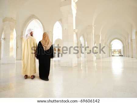 Muslim arabic couple inside big oriental empty modern building. Note: very large resolution. - stock photo